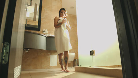 A sexy woman in a towel after taking shower in her bathroom - walking out of the Footage
