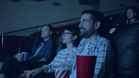 Cheerful youth men and women watching film in movie theater smiling Live Action