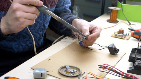 Tin Soldering Parts in Electronics Workplace Live Action