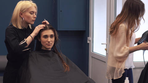 beautiful woman combing wet hair. stylist brushing woman hair in salon Footage
