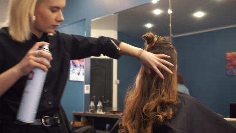 hairdresser using hairspray on client hair at salon. Hair styling. Stylist Footage