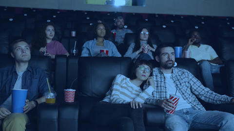 Carefree adults watching film in modern cinema holding drinks and snacks Live Action