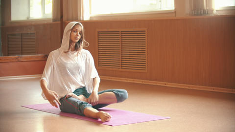 Young woman sitting on the yoga mat and sitting in lotus position Live Action