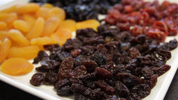 plate of dried fruit. raisins, dried apricots, prunes, dried cherries. close-up Live Action