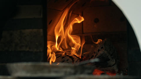 The firewood burning inside the heated oven Live Action