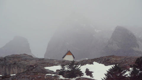 View Of Rocky Mountains With Chapel In Rainy Weather Live Action