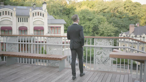 Back view of young well-dressed businessman walking on the terrace looking away Footage