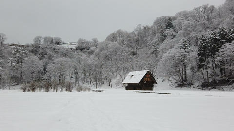 Wooden cottage in mountain village during snow falling Live Action