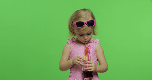 Child in pink swimsuit drinks juice cocktail with... Stock Video Footage