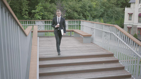 Young well-dressed businessman walking down the stairs holding netbook and cup Footage
