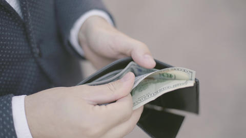 Close-up hands of young well-dressed businessman in the suit holding a wallet Footage