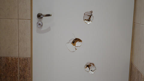 White door with holes from bullets in a hotel bathroom in Poland Live Action