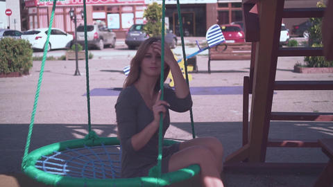 Cute young girl walks in an urban environment. Happy girl in a dress swinging on Footage