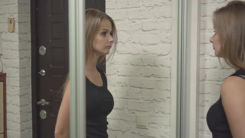A beautiful girl is standing at the front door of the house. A blonde looks Live Action