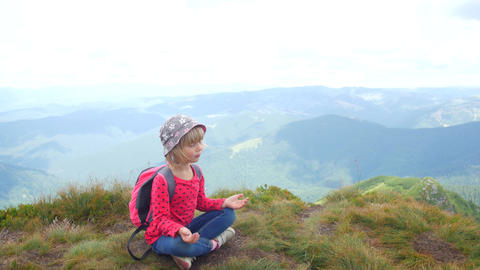 A child meditates in a lotus position on top of a mountain Footage