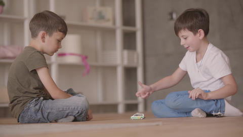 Two cute brothers sitting on the floor playing with the toy car sitting on the Live Action