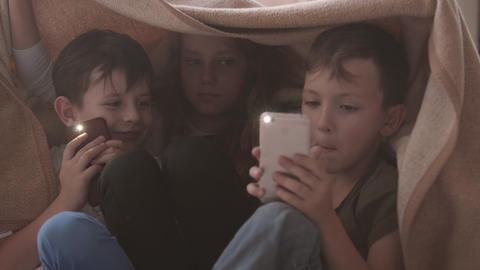Two brothers and sister sitting under the blanket playing with cellphones Live Action