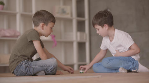 Two little brothers sitting on the floor playing with the toy car sitting on the Live Action