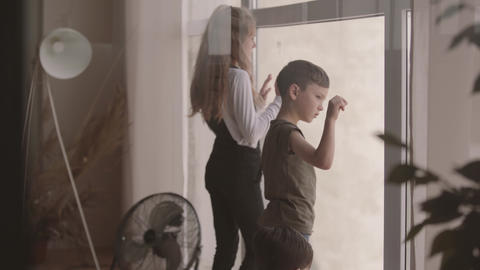 Kids look out of the wide window from home. Older sister playing at home with Live Action