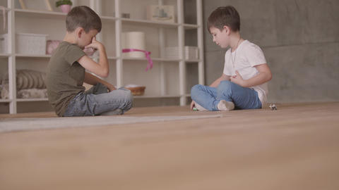 Two adorable brothers sitting on the floor playing with the toy car sitting on Live Action