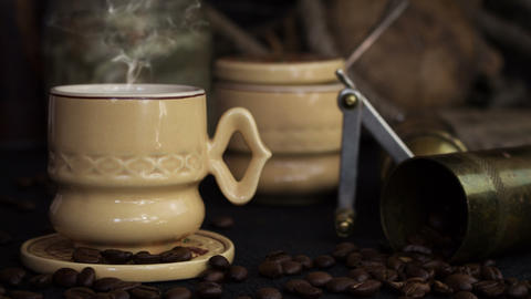 Coffee Cup Smoking Hot With Coffee Beans and Grinder On a Vintage Rustic Background Archivo