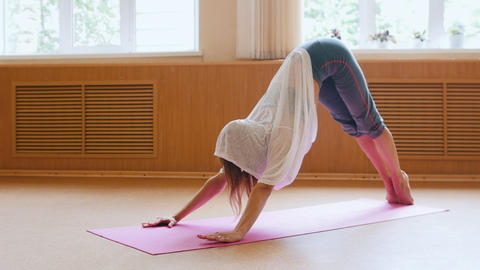 Young pretty woman exercising on the yoga mat - performing an exercising for the Live Action
