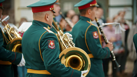 A wind instrument military parade - soldiers standing on the street and playing Live Action