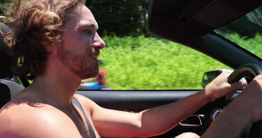 Happy carefree millennial man driving car on road trip in convertible car Live Action