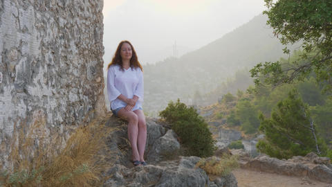 Young woman sitting on stone on cliff background. Tourist woman resting on rock Footage