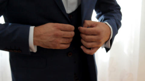 groom fastens the buttons on the suit jacket Footage