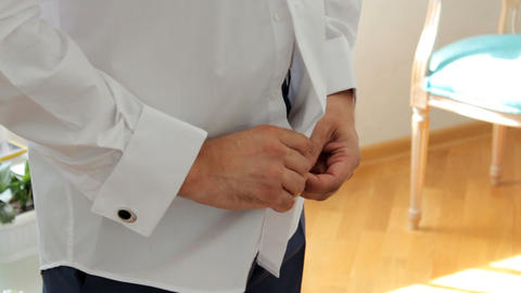 groom fastens the buttons on the shirt. body part Footage