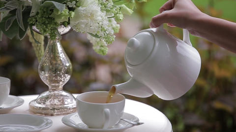 Female hand is Pouring hot tea into a white cup. Close up. Filling tea cup Live Action