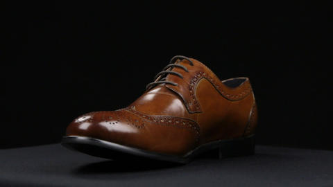Rotation of a stylish classic brown shoe with laces on a black background Live Action