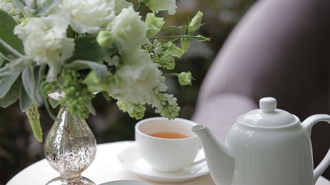 Hot tea in white cups served on a white table decorated with a bouquet of Live Action