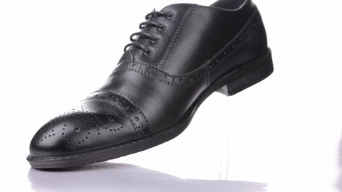 Rotation of a stylish classic black shoe with laces on a white background Live Action