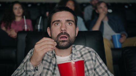 Shocked young man watching film in cinema with open mouth dropping popcorn Footage