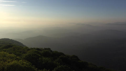 Undulate green slopes at evening mist, panoramic valley at sunset Footage