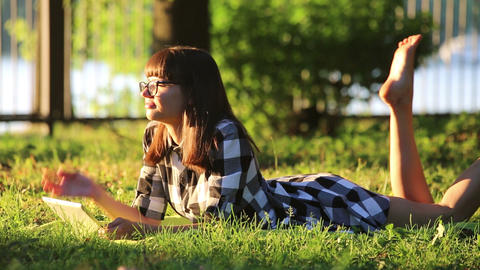 Girl is Relaxing in the Park with a Tablet PC Acción en vivo