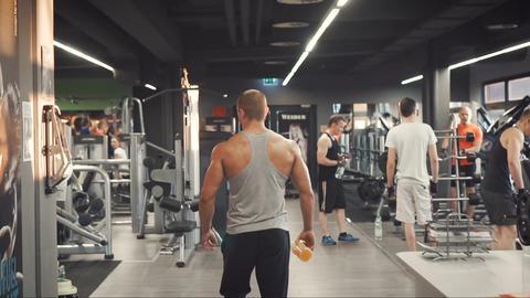 Bodybuilder walks through gym Live Action