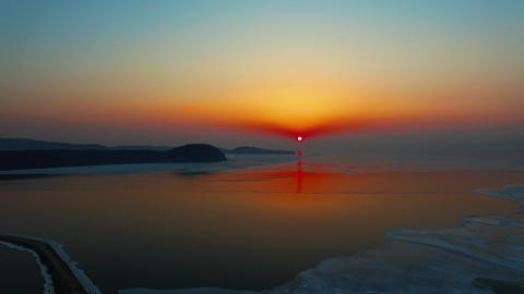 Aerial view with a beautiful sunset over the icy surface of the sea Live Action
