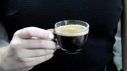 Woman in black drinks black coffee Footage