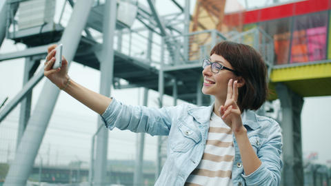 Portrait of happy young woman taking selfie with smartphone camera outside Footage