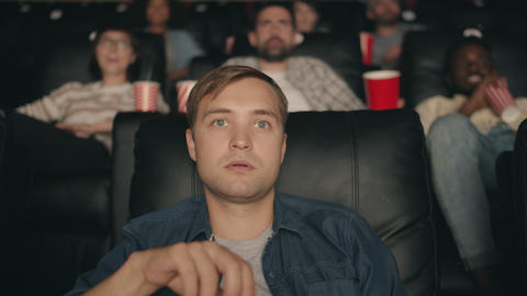 Shocked student watching film in cinema with open mouth eating popcorn smiling Live Action