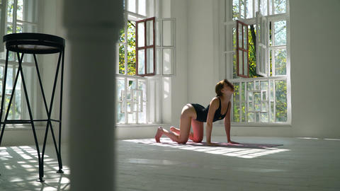 Red-haired young flexible healthy caucasian woman practicing yoga on the mat in Footage