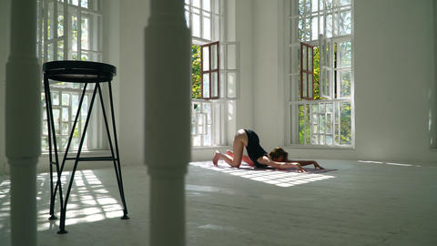 Pretty red-haired healthy caucasian woman practicing yoga on the mat in the Footage