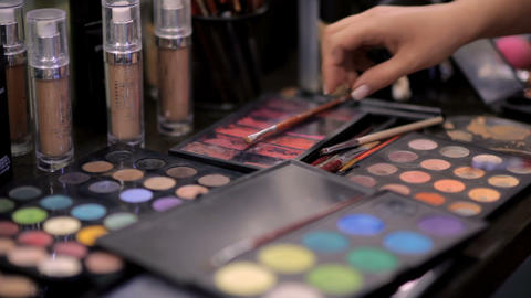 Makeup artist does makeup to a client in a beauty salon with a lot of beautiful Footage