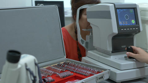 Female patient closeup eye on a eye examination modern autorefractor computer Live Action