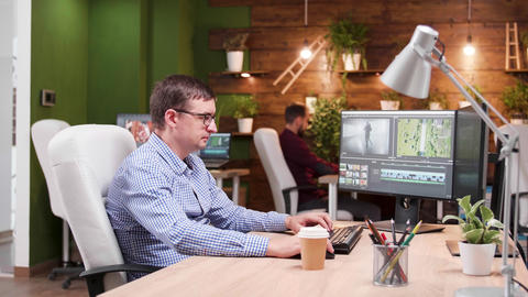 Video editor in the office working on film post production Live Action