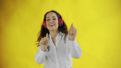 Young attractive woman listens to music with headphones and smiles in Studio Live Action