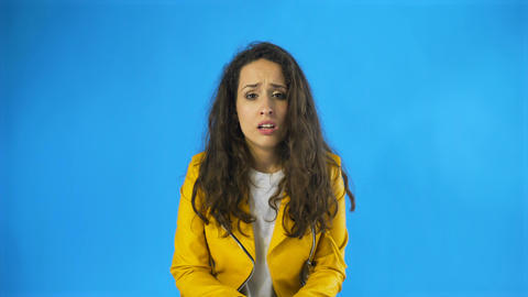Very sad young woman almost crying in Studio with blue Background Footage